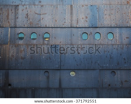 Rusty weather beaten steel ship hull - stock photo