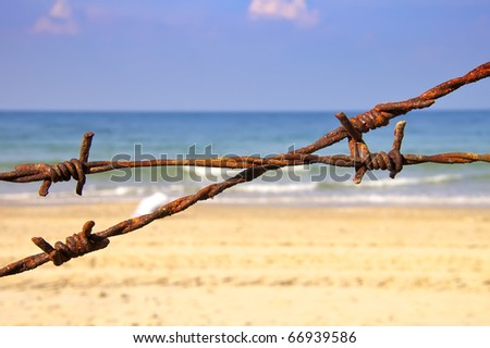 Rusty wire fence on the beach, selective focus - stock photo