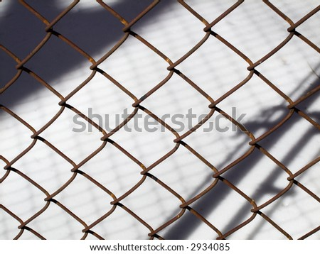 Rusty woven wire fence against snow background