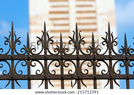 Rusty Wrought Iron Fence / Old and rusty wrought iron fence on blue sky and blurry architecture - stock photo
