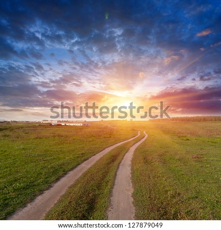 rut road in steppe on sunset background - stock photo