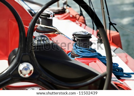 Rutter of a red sail boat in the foreground with a winch and blue rope in the background. - stock photo