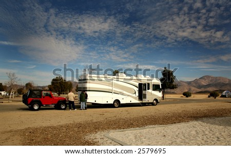 RV Coach Towing an Offroad 4X4 Vehicle - stock photo