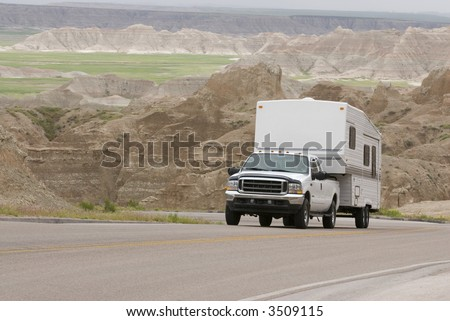 RV pick-up truck and trailer climbing scenic mountain road in the Badlands - stock photo