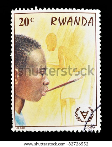 RWANDA - CIRCA 1981: A stamp printed in Rwuanda that shows a young man painting with his mouth, circa 1981 - stock photo