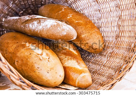 Rye and wheat bread loafs in a rustic braided basket - stock photo