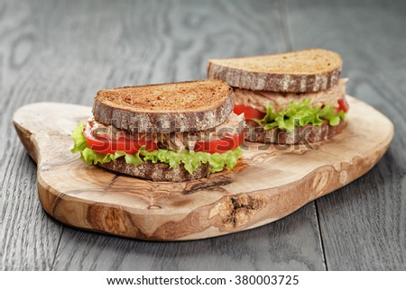 rye bread sandwich with tuna and vegetables on wood background - stock photo