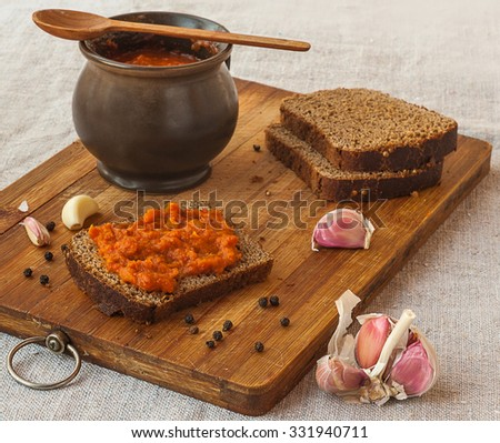 Rye bread spread with spicy stuffed peppers, tomatoes, carrots, garlic and apples on a cutting board - stock photo