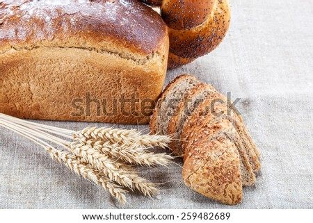 Rye bread, wheat loaf with poppy seeds and ears on sacking. - stock photo