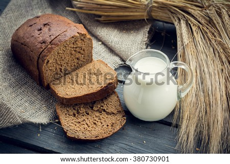 Rye bread with barley sheaf and jug of milk on wooden background