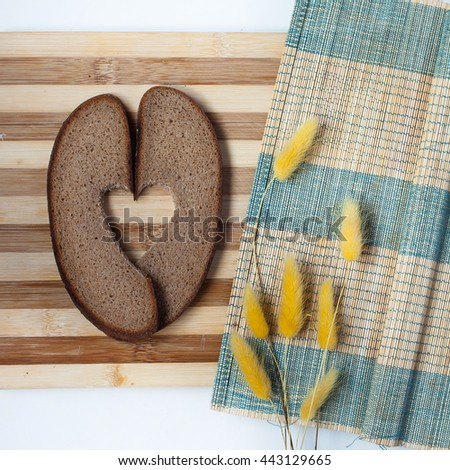 Rye bread with heart on a wooden board - stock photo