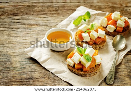 rye bruschetta with honey pumpkin and goat cheese on a dark wood background. tinting. selective focus on mint on the front bruschetta - stock photo