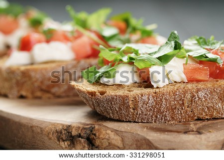 rye bruschetta with mozzarella, tomatoes and parsley, selective focus - stock photo