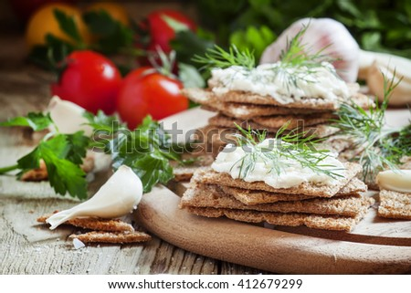 Rye crispbread with garlic sauce and herbs, selective focus - stock photo