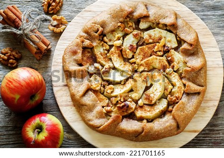 rye galette with apple, cinnamon and walnuts on a dark background. tinting. selective on the middle of galette - stock photo