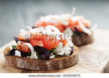 rye sandwich or bruschetta with ricotta, herbs and tomato on wooden table - stock photo