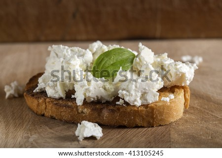 Rye sandwiches or bruschetta with ricotta cheese and basil on wooden board - stock photo