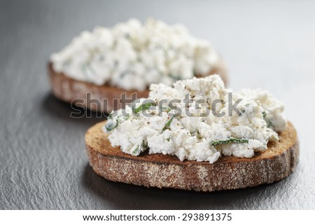 rye sandwiches or bruschetta with ricotta cheese and herbs on slate board - stock photo