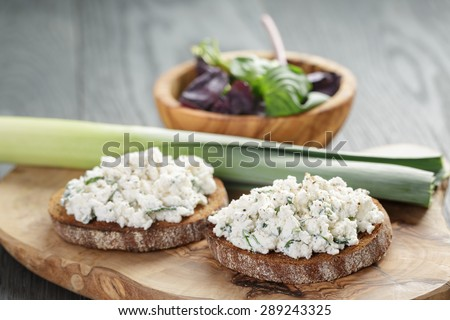 rye sandwiches or bruschetta with ricotta cheese and herbs on wooden table - stock photo