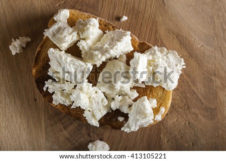 Rye sandwiches or bruschetta with ricotta cheese on wooden board - stock photo