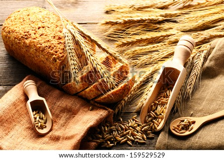 Rye spikelets and bread on wooden background - stock photo