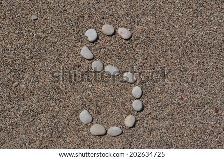 S letter made of stones on sand  - stock photo