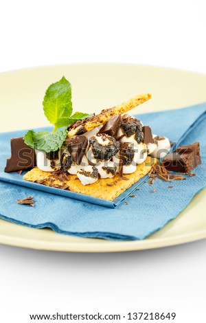 S'more on plate with chocolate and marshmellows ready to be eaten - stock photo