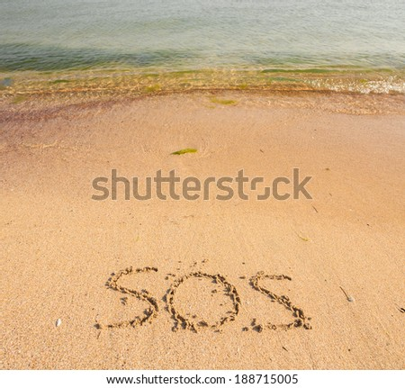 S.O.S written in the sand - stock photo
