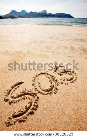 S.O.S written in the sand of an island with the ocean in the distance - stock photo