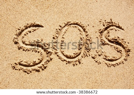 S.O.S written in the sand with a finger or stick - stock photo