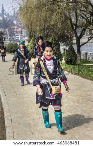 SA PA, VIETNAM - MARCH 12, 2016: A woman of the Hmong tribe is walking along a street of Sa Pa, Vietnam. In the background is the city.