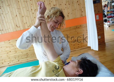 SAALFELDEN, AUSTRIA - AUGUST 30: physical therapist exercising with senior rheumatism patient on August 30, 2007 at rehabilitation center in Saalfelden, Austria.