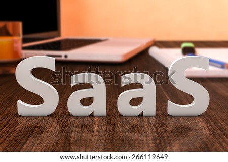 SaaS - Software as a Service - letters on wooden desk with laptop computer and a notebook. 3d render illustration. - stock photo