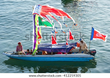 Sabah, Malaysia - April 23, 2016:A family of Bajau ethnic inside the Traditional Bajau's boat called Lepa Lepa decorated with colorfull Sambulayang flag during Regatta Lepa Festival in Semporna Sabah.