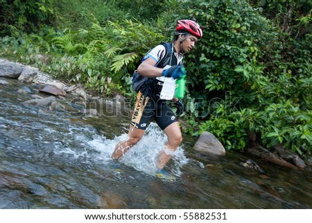 SABAH, MALAYSIA - APRIL 2ND.  A racer from a participating team makes his way across a river in the morning hours at the Sabah Adventure Challenge, April 2nd, 2010, Sabah, Malaysia.
