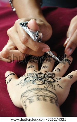 SABAH, MALAYSIA - 30 MAY, 2015: Female henna artist applies a henna design to the back of a woman's hands in Kota Kinabalu, Sabah Malaysia. - stock photo