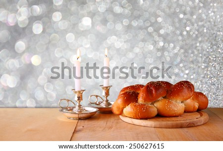 Sabbath image. challah bread and candelas on wooden table with glitter background  - stock photo