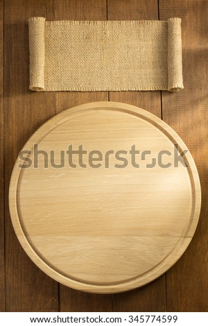 sack burlap and cutting board on wooden background - stock photo
