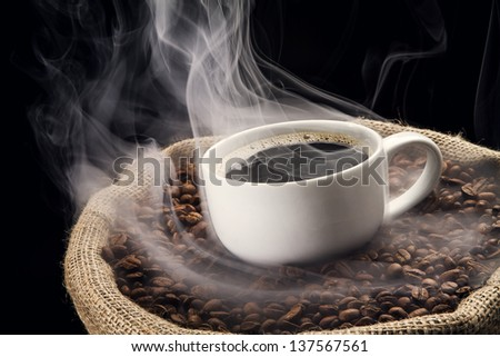 Sack full of still hot, freshly roasted coffee beans with the mug in the middle. - stock photo