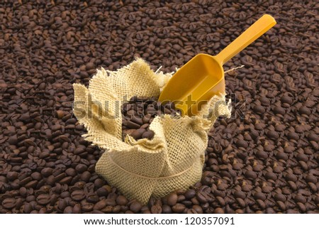Sack of coffee beans and scoop with coffee beans background - stock photo
