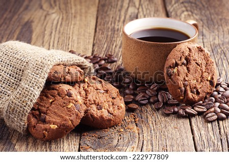 Sack with chocolate cookies and cup of hot coffee on old wooden table - stock photo
