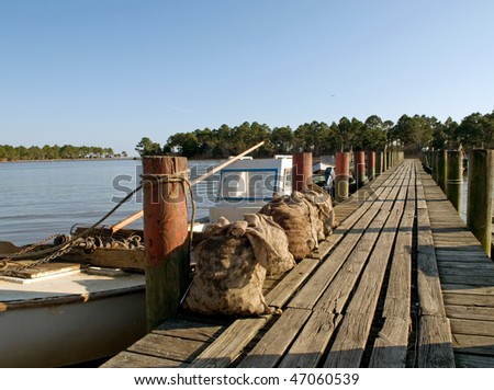 Sacks of harvested oysters on a dock, Florida panhandle - stock photo