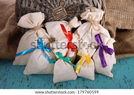 Sacks on color wooden table, on sackcloth background