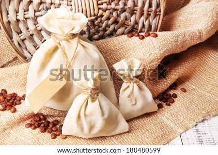 Sacks with coffee beans on wooden table, on sackcloth background