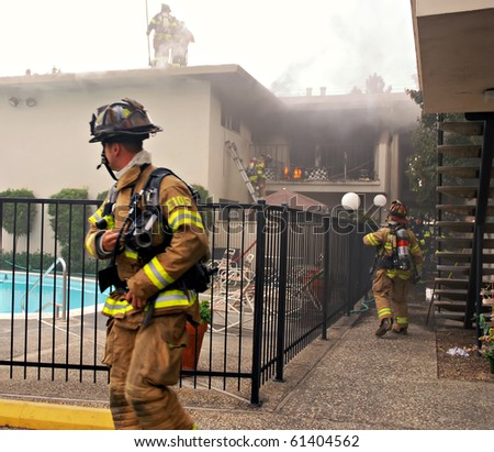 SACRAMENTO, CA - AUGUST 28: Sacramento Metro Fire District firefighters rush to rescue a 4-year-old boy from his burning apartment August 28, 2010 in Sacramento, California. - stock photo