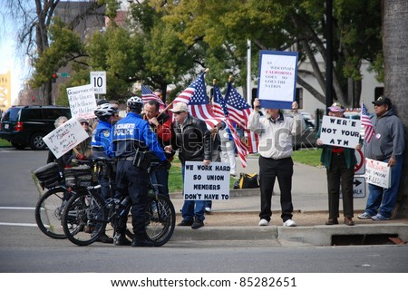 SACRAMENTO, CALIFORNIA - FEBRUARY 26: Law Enforcement officers talk to Tea Party protesters rallying in Sacramento, California on February 26, 2011