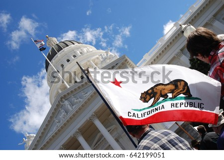 "SACRAMENTO, CALIFORNIA, USA - February 26, 2011: Labor union supporter carries California state flag at the California State Capitol during ""Rally to Save the American"
