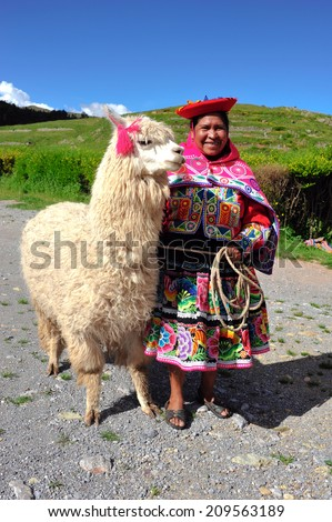 SACSAYHUAMAN, CUSCO, PERU - MARCH 8, 2010: Peruvian woman in traditional dresses standing with a big Alpaca. Alpacas fiber is used for making knitted and woven items, similar to wool. - stock photo