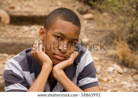 Sad African-American Male sitting in outdoor setting - stock photo