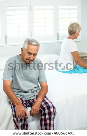 Sad aged man sitting on bed with woman at home - stock photo